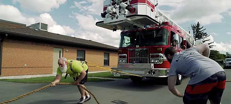 Bild: Kevin Fast, wie er ein Feuerwehrauto bei seinem Training zieht